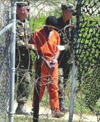 A detainee is walked by two US Army military policemen at Camp X-Ray in Guantanamo Bay, Cuba, in 2002. (Photo: AFP)