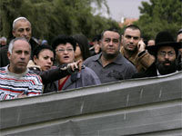 Israeli onlookers stand at the scene of a rocket attack in Ashkelon(Credit: Reuters)