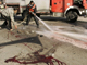 A Palestinian firefighter uses a hose to clean blood on a street in Gaza (Photo: Reuters)