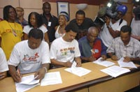 LPK union leader Elie Domota (2nd L) signs an agreement with two employer groups, Pointe-a-Pitre, Feb. 26, 2009.  Photo: REUTERS/Gilles Petit