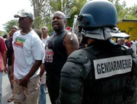 Gendarmes stand guard near a group of protest supporters in Guadeloupe(Credit: Reuters)
