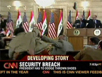 A still from the pool video (CNN) showing President Bush (podium, left) ducking the shoes (top right)(Photo: AFP)