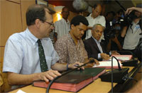 Guadeloupe prefect Nicolas Desforges (l) and strike leader Elie Domota (c) sign a deal ending the strike, Pointe-a-Pitre, 4 March 2009(Photo: Reuters)