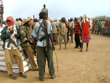 Somali militants stand guard as internally displaced people await food aid in Torotow on 13 April 2009(Photo: Reuters)