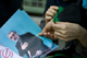 A woman ties a green symbolic ribbon for her friend as she holds a picture of Iran's Presidential candidate Mirhossein Mousavi, during a rally in front of the Tehran Governor's office(Photo: Reuters)