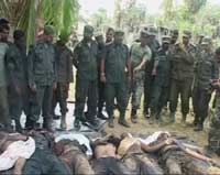 Soldiers stand over LTTE bodies. Image shown on Derana TV, 18 May 2009REUTERS/Derana TV