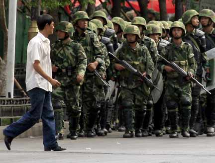 An ethnic Uighur man walks in front of Chinese paramilitary police in Urumqi(Photo:Reuters)