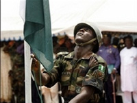 A Nigerian soldier lowers the Nigerian flag.(Photo: Dibussi Tande/Wikimedia Commons)