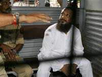 Mohammad Haneef Sayyed sits in a police van on his way to the court in Mumbai.(Photo : Reuters)