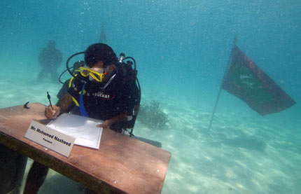 Maldives President Mohamed Nasheed signs a declaration during the first underwater cabinet meeting in the Maldives(Photo: Reuters/Government handout)