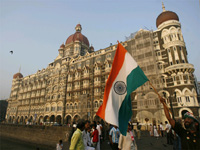 A man walks with the Indian national flag Thursday in front of the Taj Mahal hotel(Photo: Reuters)
