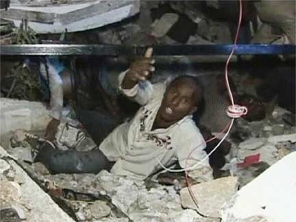 A man trapped under the rubble calls for help at Port-au-Prince University(Credit: Reuters)