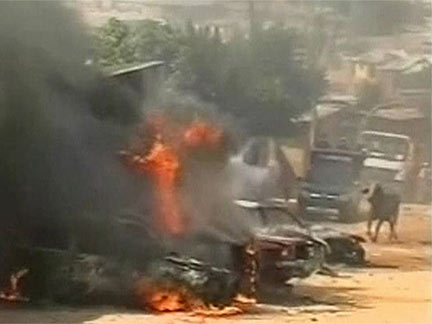 Vehicles burning on the street in Jos(Credit: Reuters)